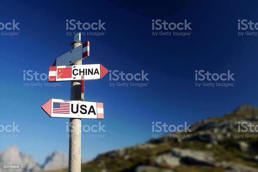 USA and Chinese flags on mountain signpost. stock photo