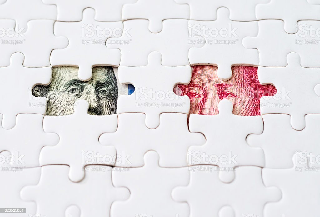 US and Chinese paper currency under jigsaw puzzle stock photo
