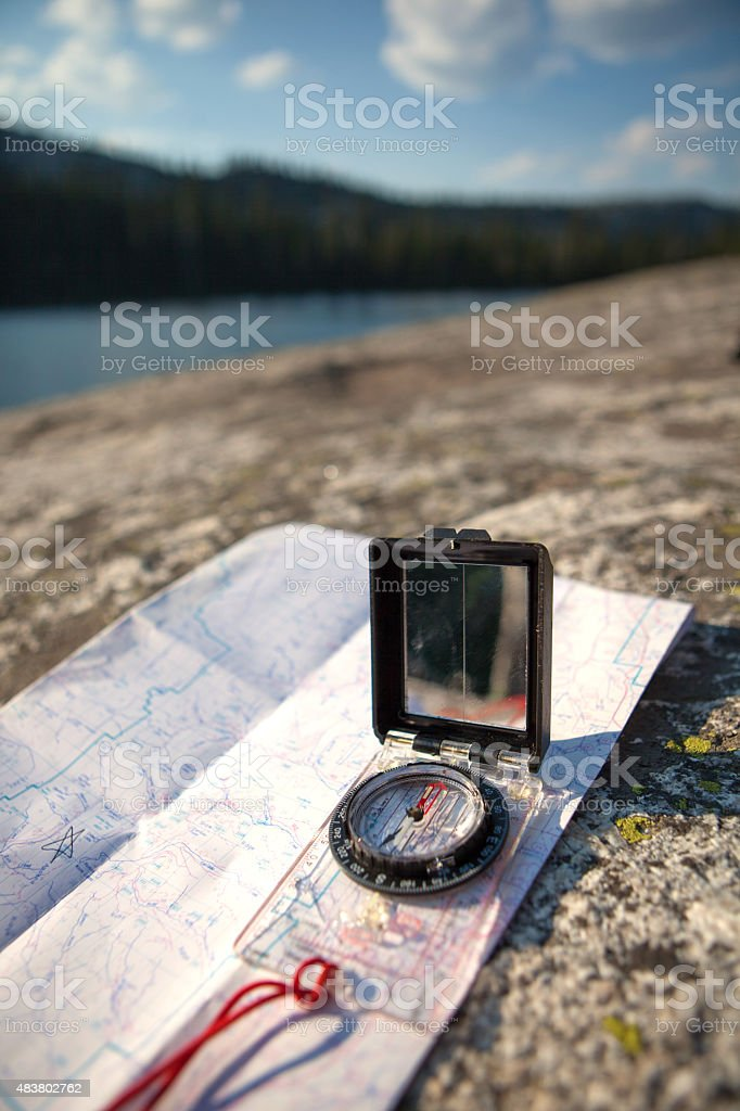 GPS and Compass on a map in the backcountry. stock photo