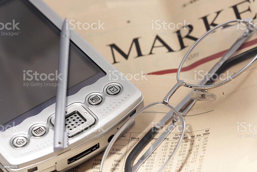 PDA and glasses on a newspaper royalty-free stock photo