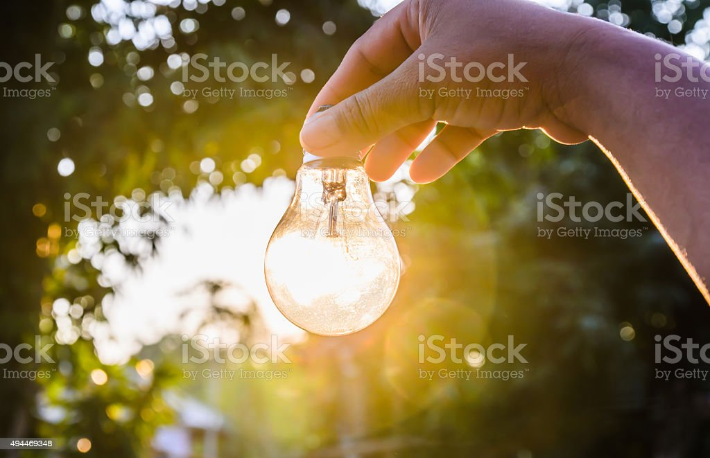 and holding a light bulb with sunset power concept stock photo