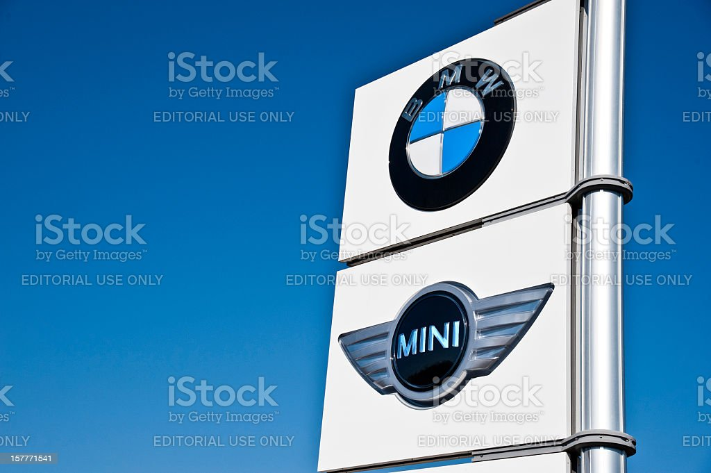 BMW and Mini Cooper Sign Against Sky stock photo