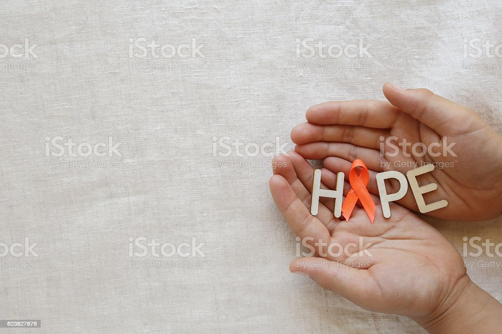 HOPE and orange Ribbons on hands, Leukemia awareness, Self Injur stock photo