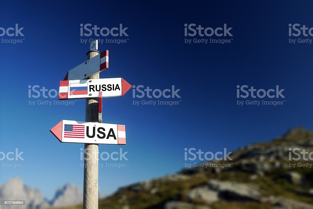 USA and Russian flags on mountain signpost. stock photo