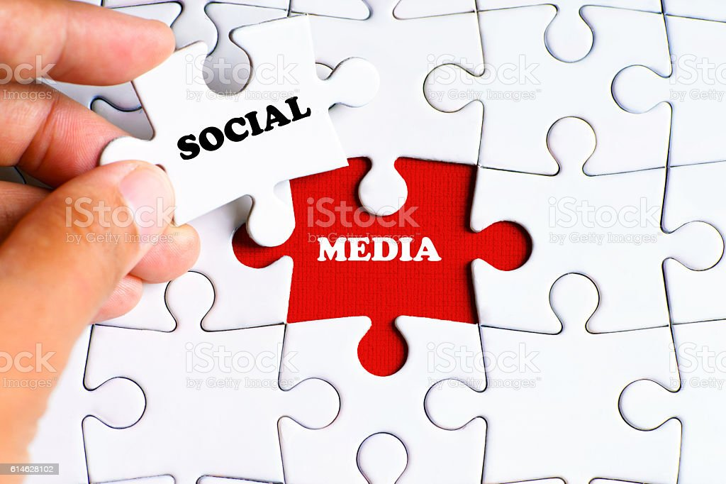 'MEDIA and SOCIAL' word on missing puzzle with a hand stock photo