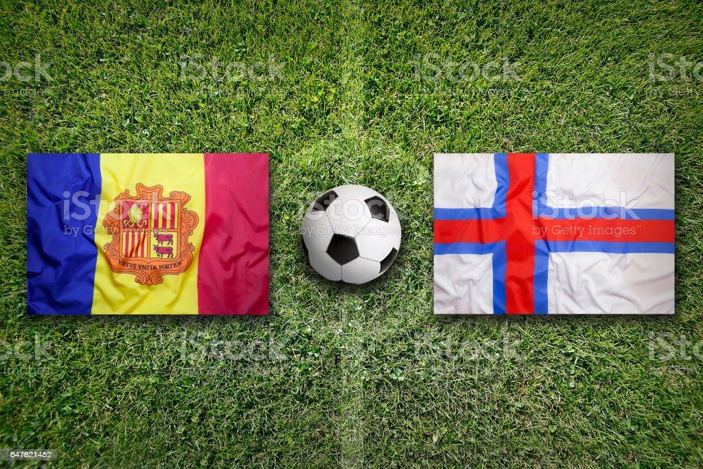 Andorra vs. Faroe Islands flags on soccer field stock photo