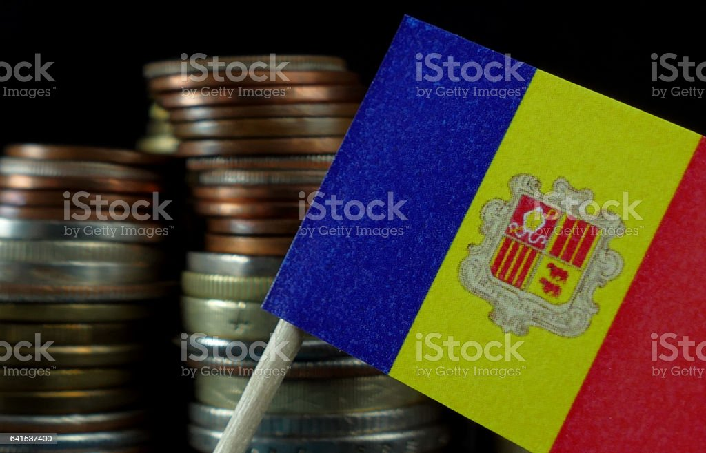 Andorran flag waving with stack of money coins macro stock photo
