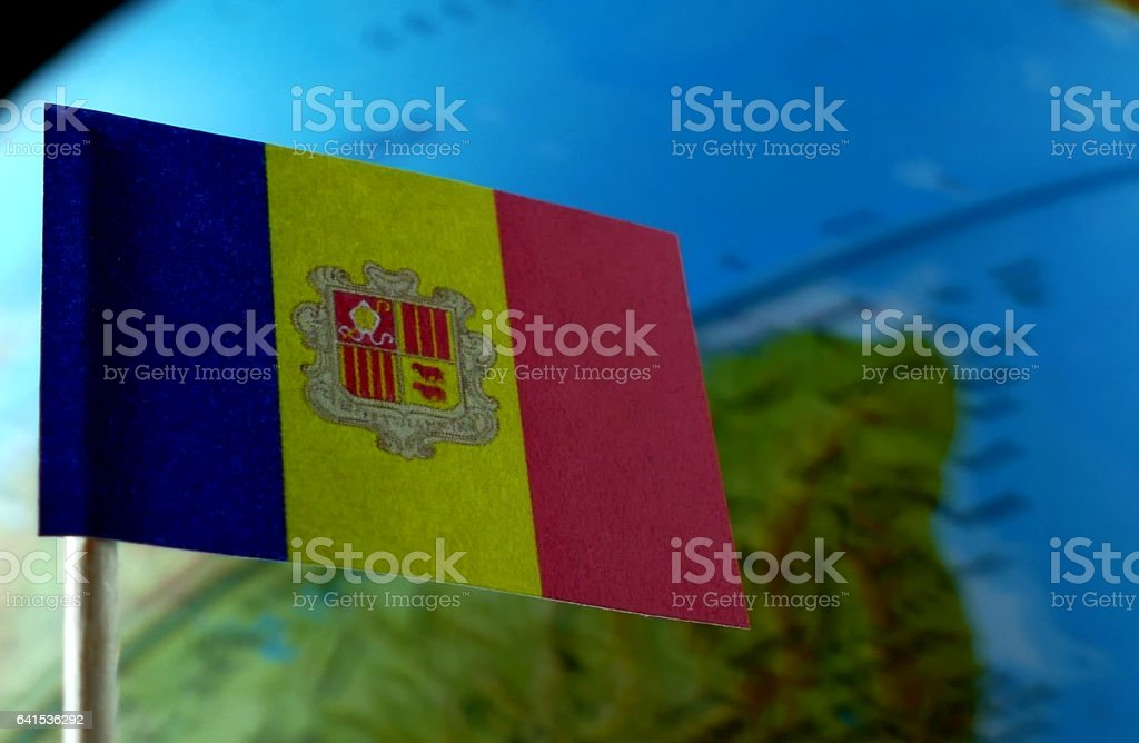Andorran flag with a globe map as a background macro stock photo
