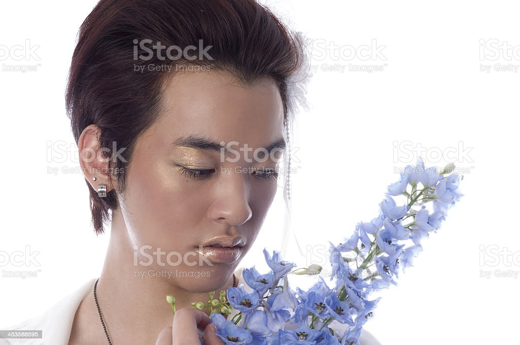 Androgynous Asian man in golden makeup with delphinium. royalty-free stock photo