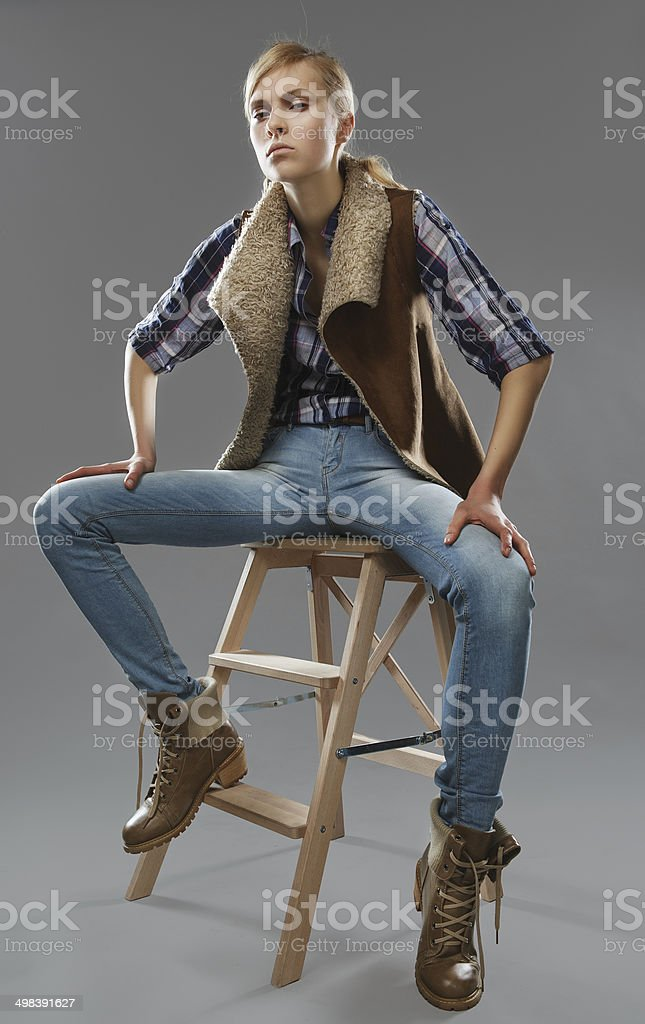 androgynous girl sits on a chair. Jeans and jacket. royalty-free stock photo