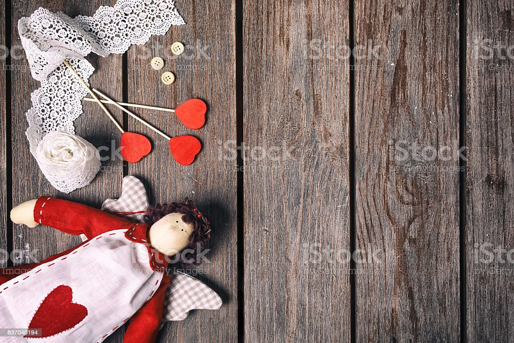 Angel a soft toy with heart, lace ribbon, buttons and stock photo