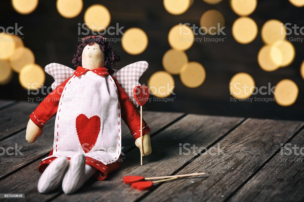 Angel a soft toy with heart sitting on old wood stock photo