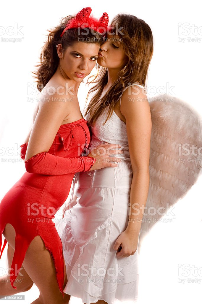 angel and devil kissing stock photo