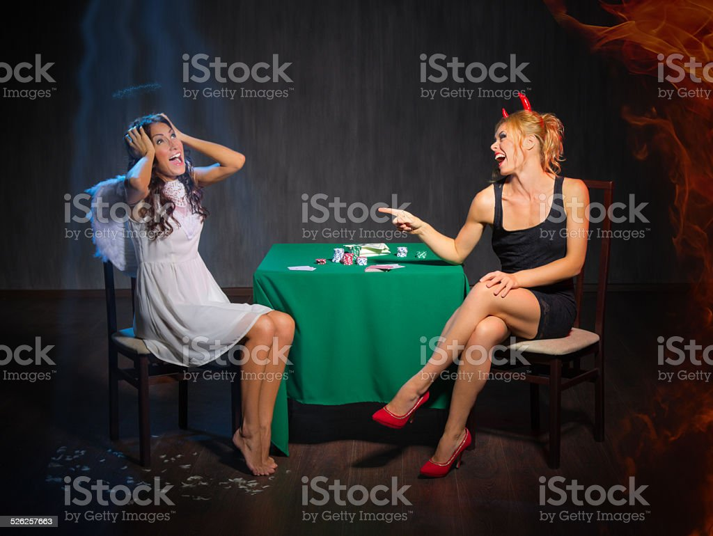 Angel and devil playing cards stock photo