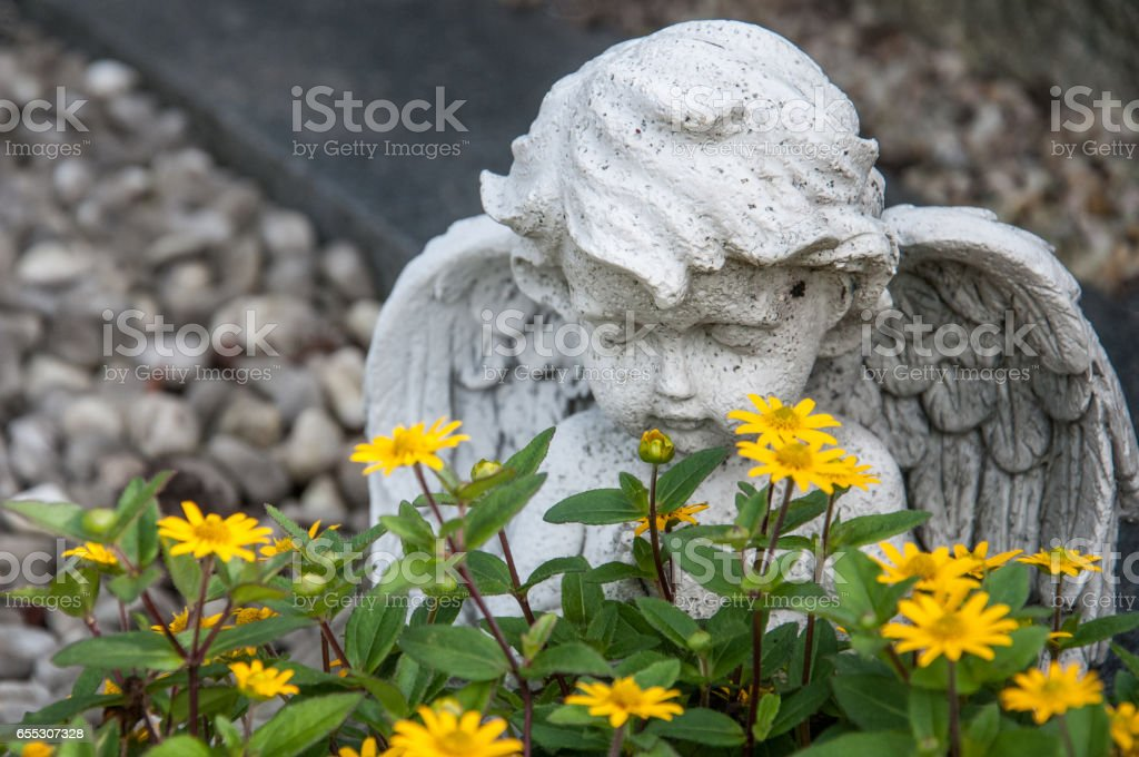 angel and yellow flowers on a grave stock photo