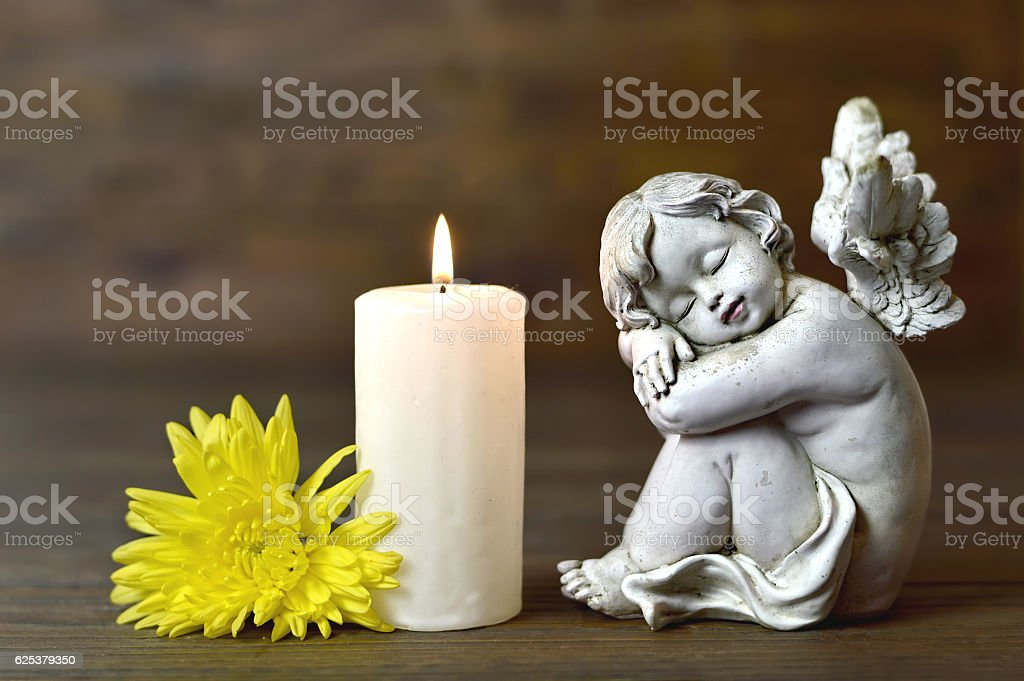 Angel, candle and flower on wooden background stock photo