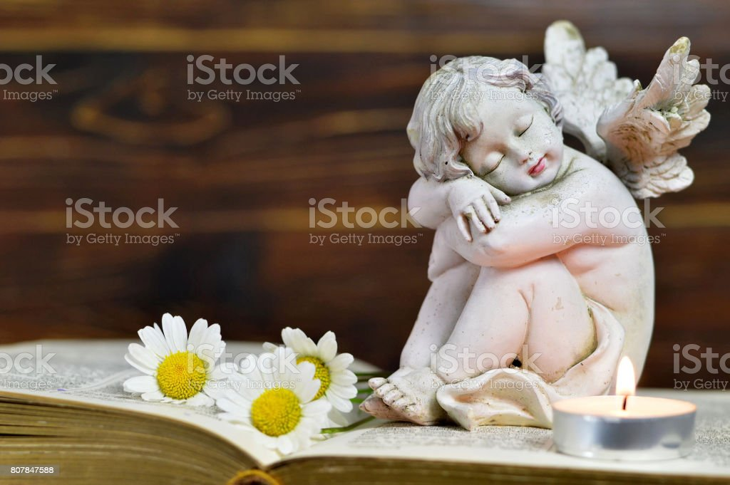 Angel, candle and flowers stock photo