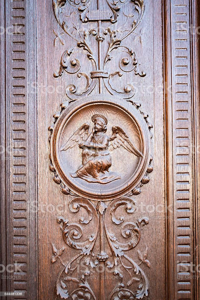 Angel engraved on the wooden portal of an ancient church. stock photo