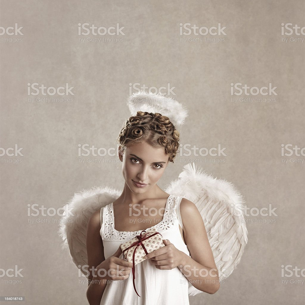 angel holding a wrapped gift stock photo