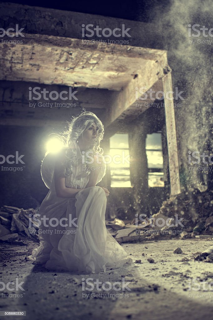 Angel in white dress posing in a ruin. stock photo