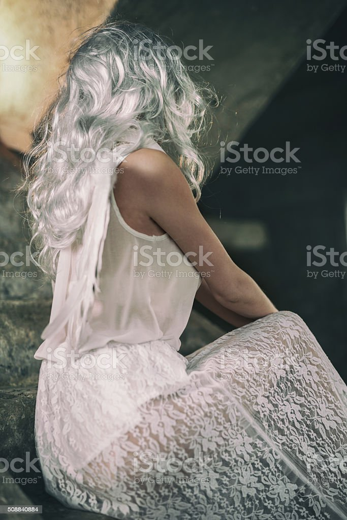 Angel in white on stairs with obscured face. stock photo