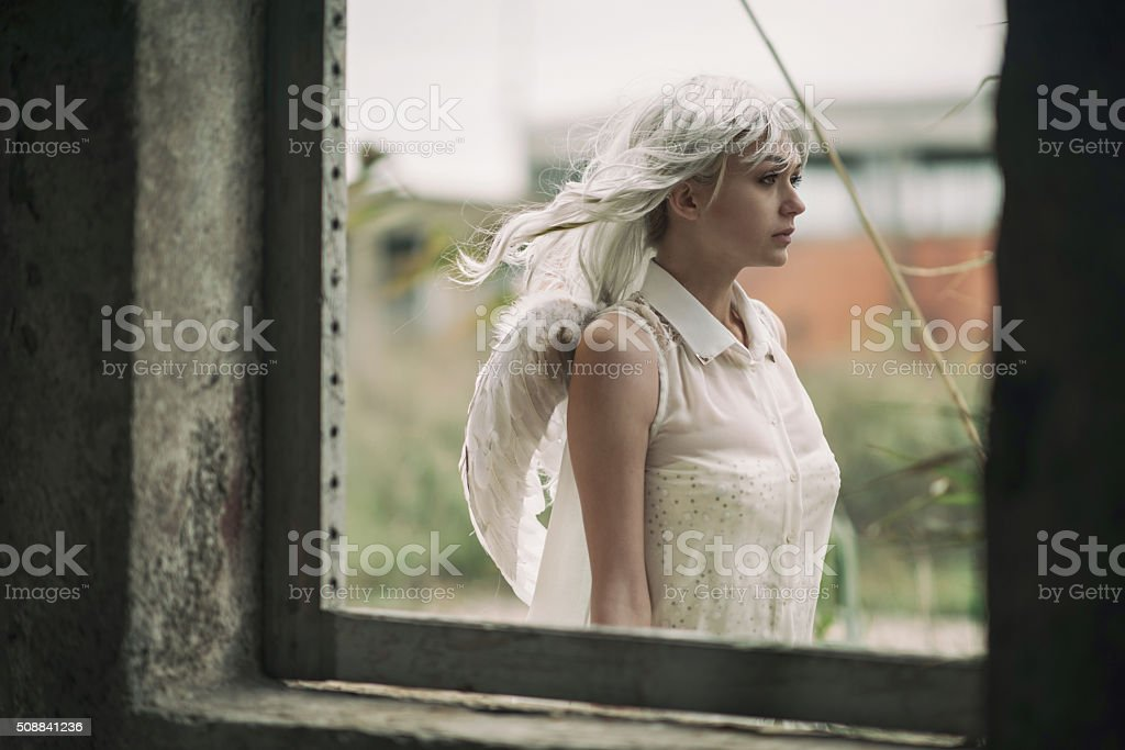 Angel in white walking by the window. stock photo