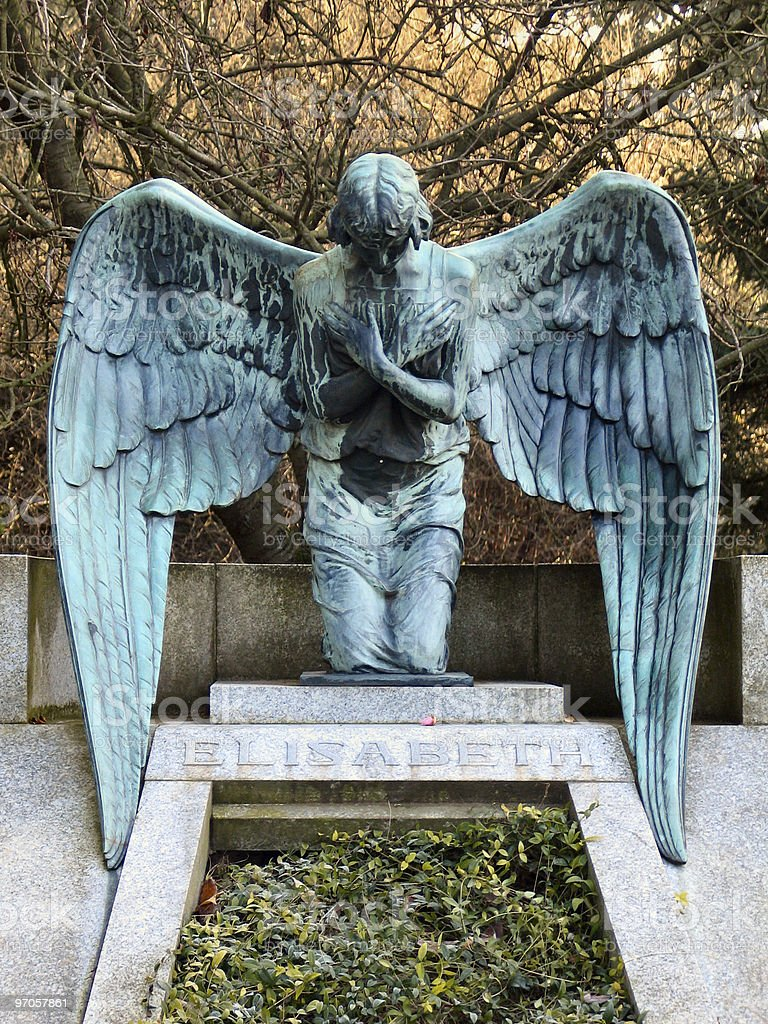 Angel kneeing on a grave stock photo