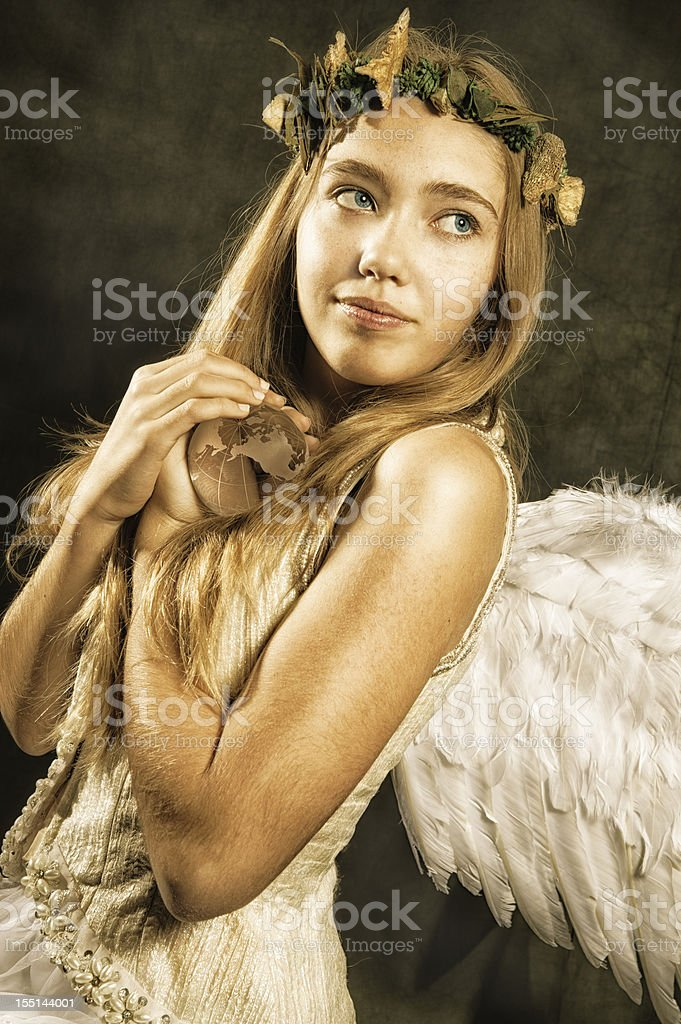 Angel of Nature holding earth. stock photo