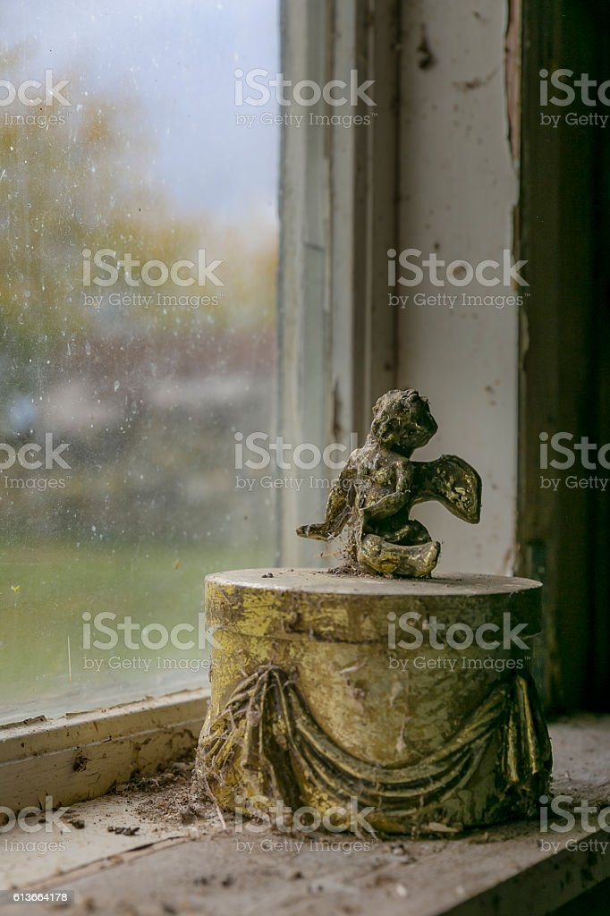 Angel on a box in decaying enviroment stock photo