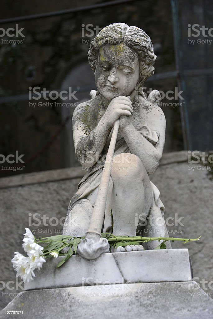 Angel on the old graveyard headstone and flowers royalty-free stock photo