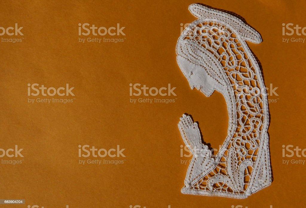Angel shaped Lace work on textile background stock photo
