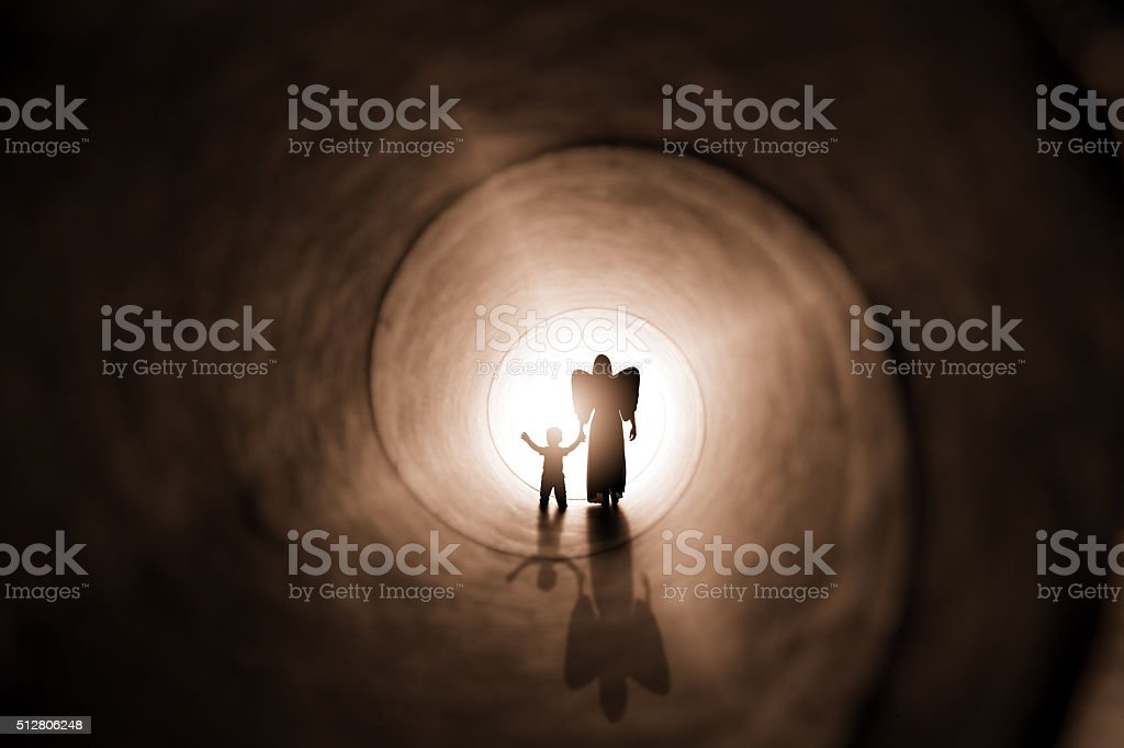 Angel Walking Child To Light stock photo