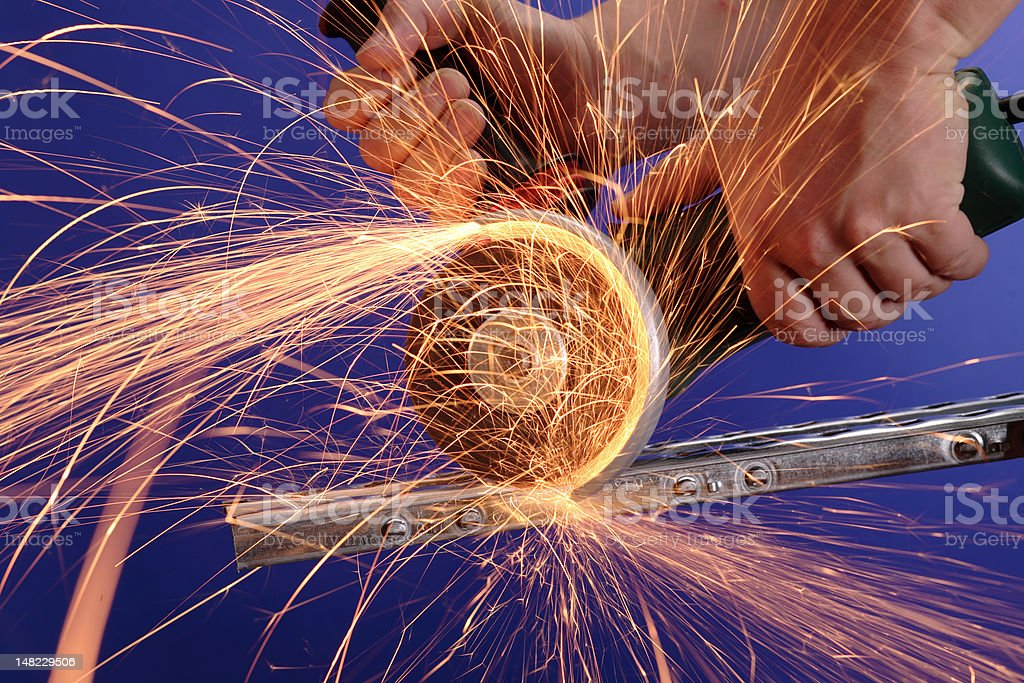 Angle grinder in action, blue background royalty-free stock photo