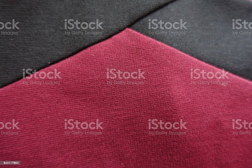 Angle of black ribbons on maroon fabric stock photo