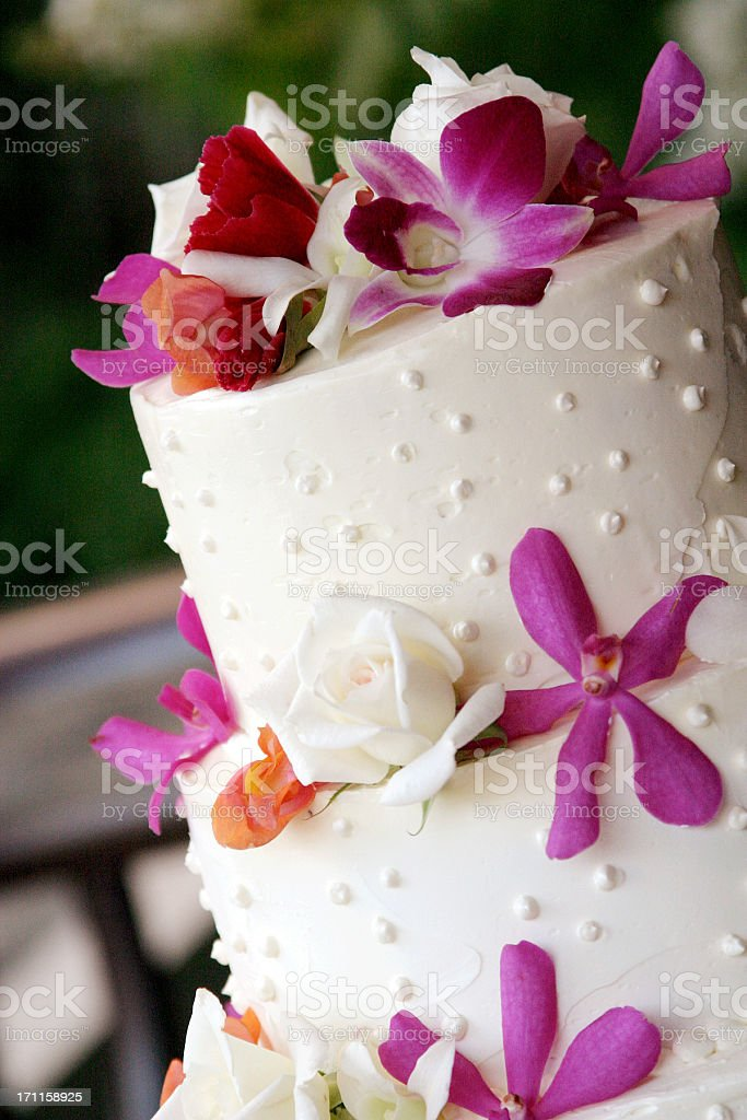 Angled Close-up of Flowers Decorating White Tiered Wedding Cake royalty-free stock photo