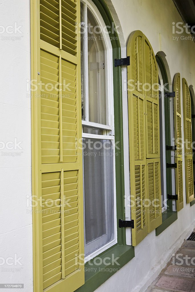 angled line of windows with lime green shutters royalty-free stock photo
