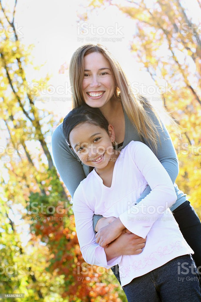 Angled outdoor portrait of mother and daughter embracing stock photo