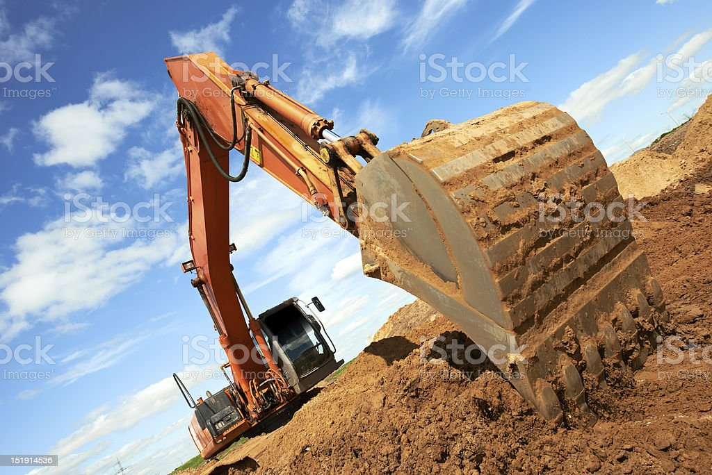 Angled photo of excavator arm digging in a dirt pile stock photo