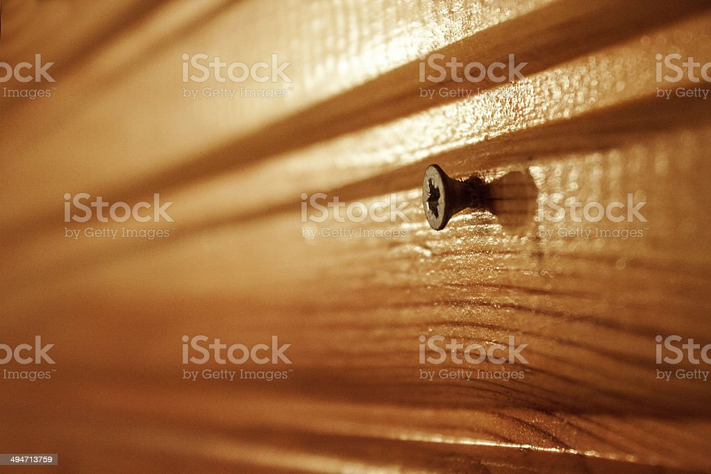 Angled screw on illuminated wooden surface stock photo