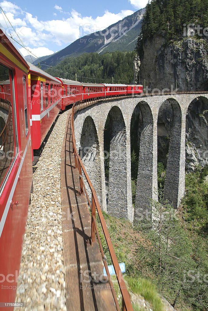 Angled view of Bernina Express train in red on a bridge royalty-free stock photo