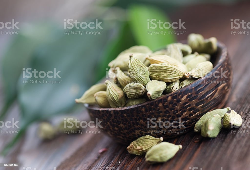 Angled view of cardamom spices in wooden bowl stock photo