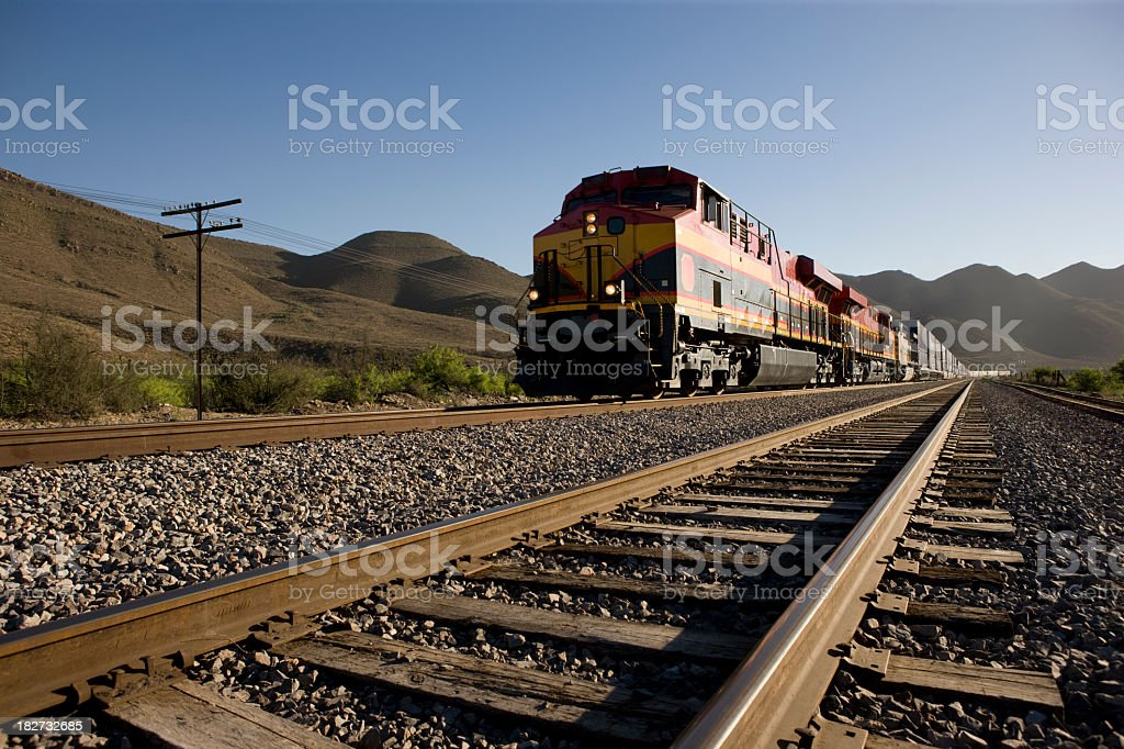 Angled view of train tracks with oncoming freight train stock photo
