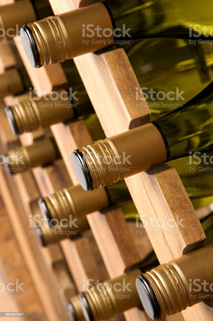 Angled view of white Wine bottle necks in a rack. royalty-free stock photo