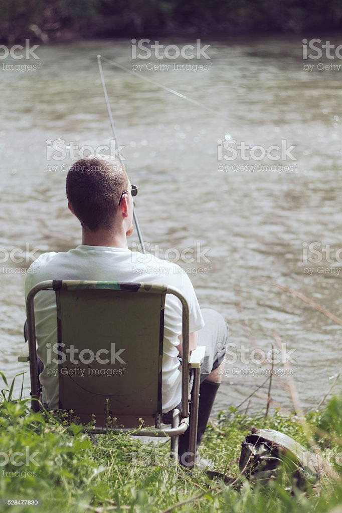 Angler sitting restingly in camping chair in springtime stock photo