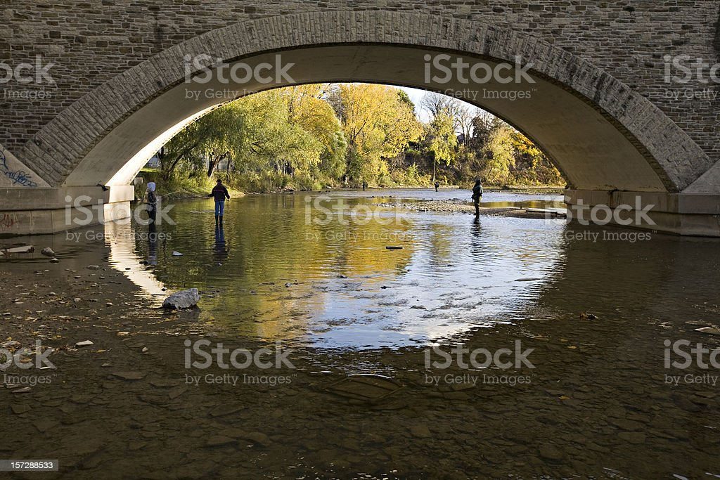 Anglers fishing under bridge during Fall stock photo