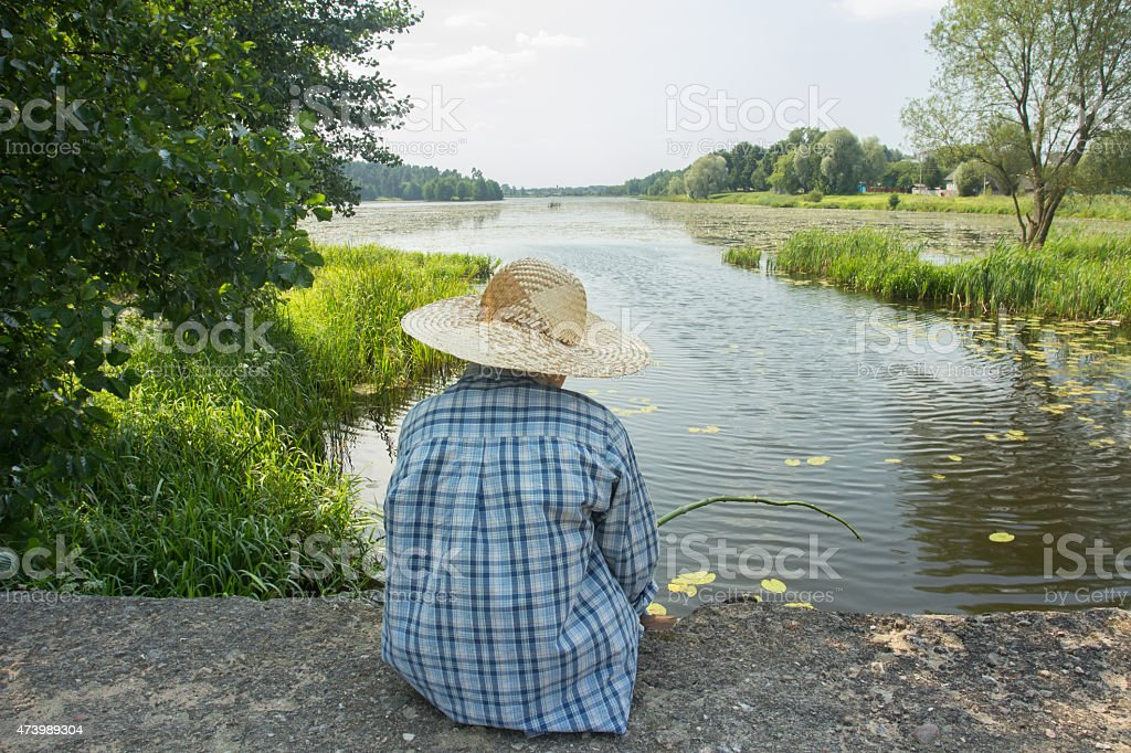 Angling boy with fishing rod on concrete bridge back view stock photo