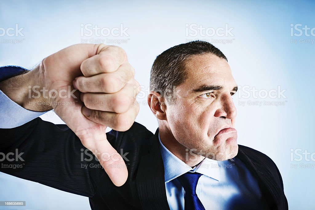 Angrily frowning businessman makes thumbs-down signal stock photo