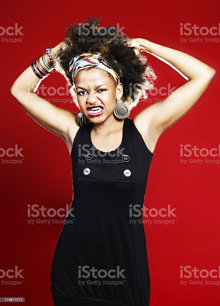 Angrily grimacing afro-haired woman tears her hair out in rage royalty-free stock photo