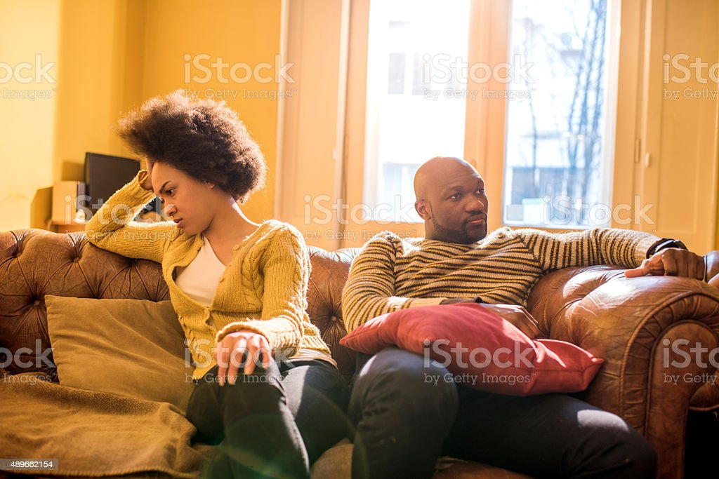Angry African American couple ignoring each other after a fight. stock photo