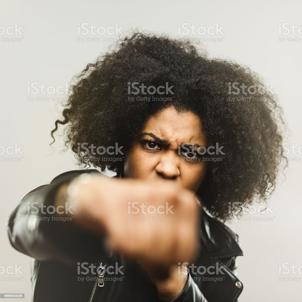 Angry african american woman punching at camera stock photo
